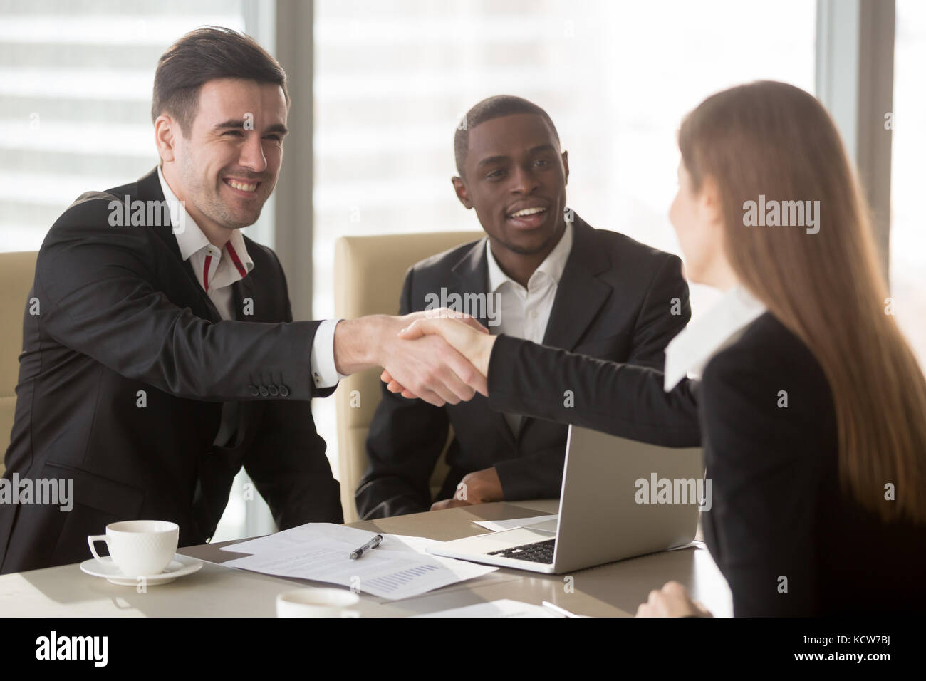 Happy smiling caucasian and afro american businessmen handshaking with female job applicant or businesswoman on - Stock Image