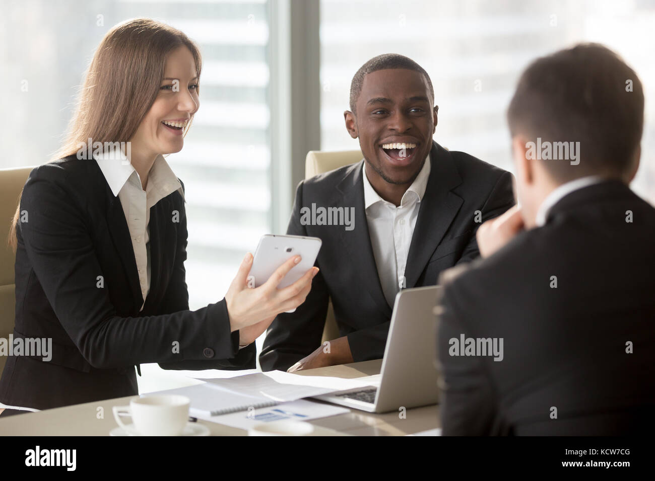 Happy smiling caucasian businesswoman using digital tablet at negotiations with multinational partners, laughing - Stock Image