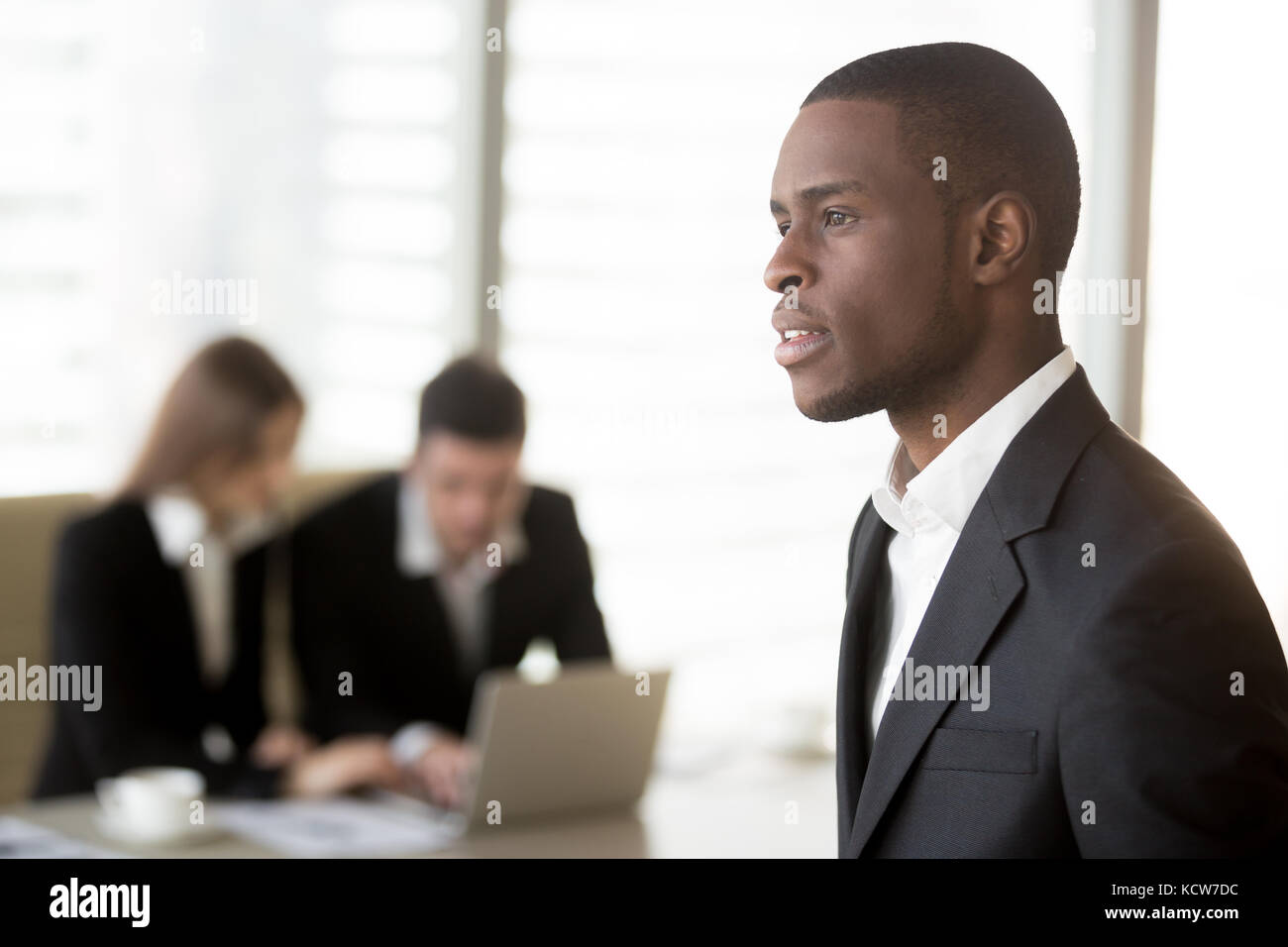 Side view portrait of handsome black businessman looking in distance, caucasian businesspersons working on laptop - Stock Image