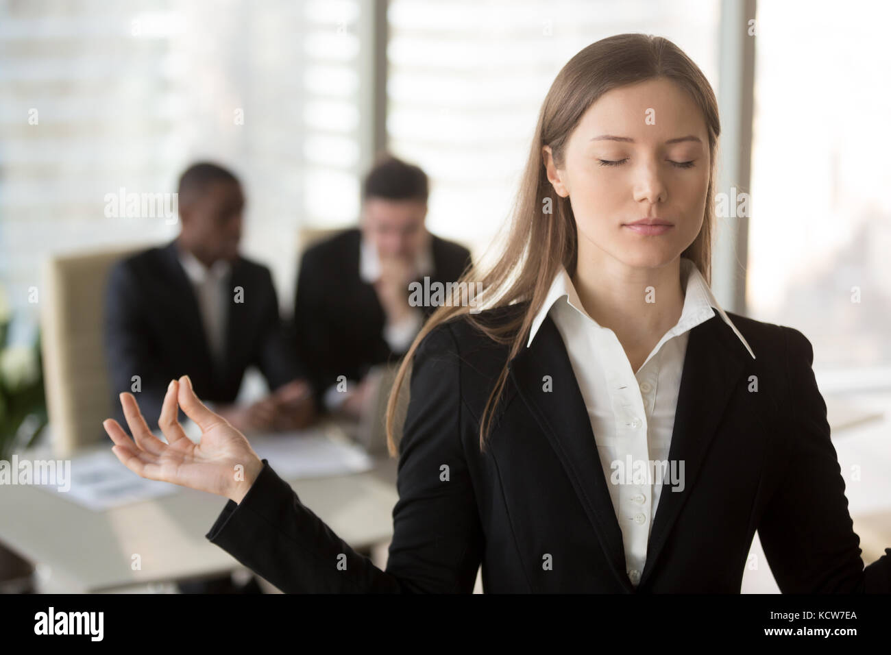 Portrait of attractive female office worker trying to keep calm in difficult situation at work. Businesswoman meditating - Stock Image