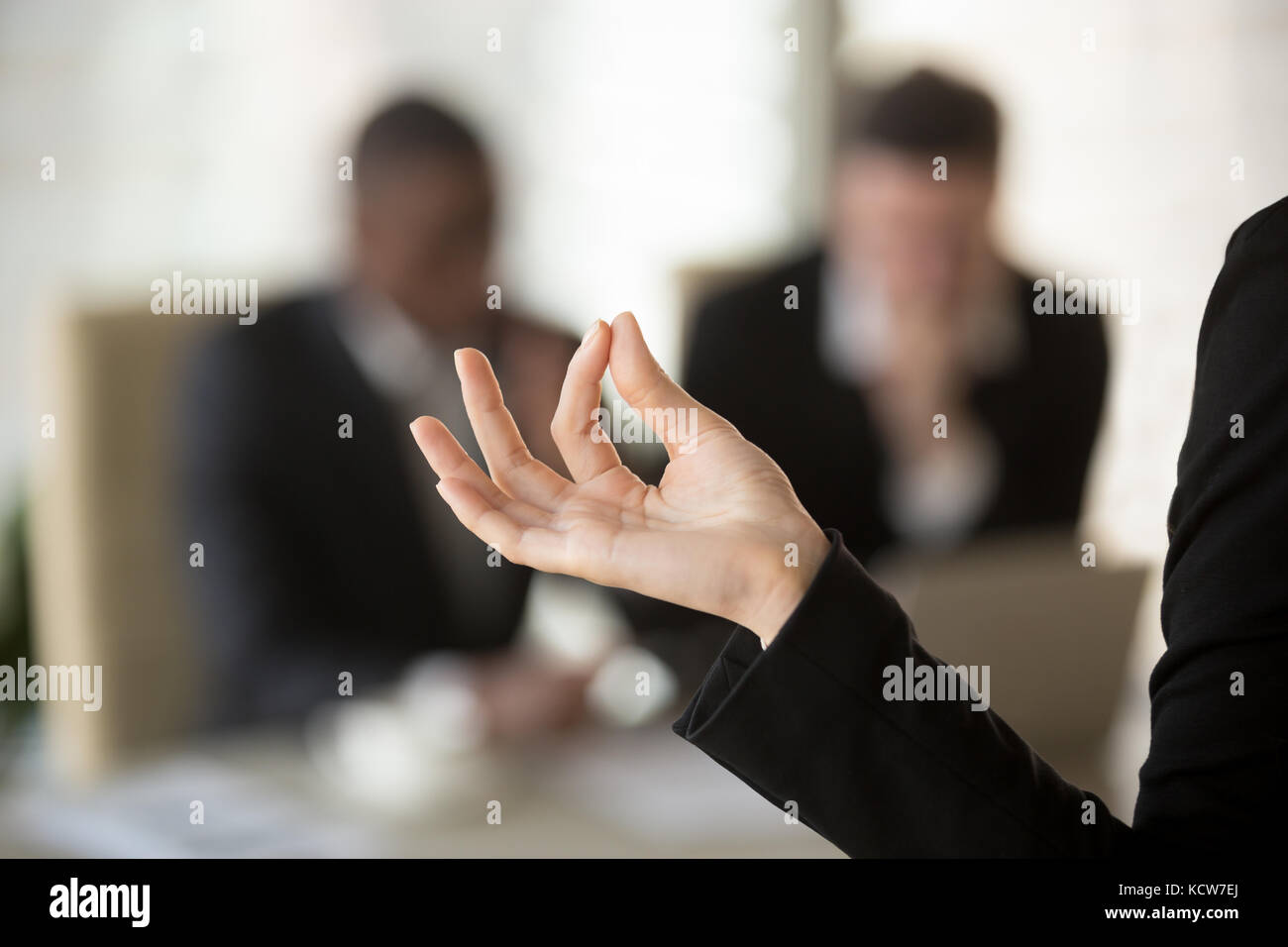 Close up image of female palm with fingers folded in Jnana mudra gesture with blurred silhouettes of talking businessmen - Stock Image