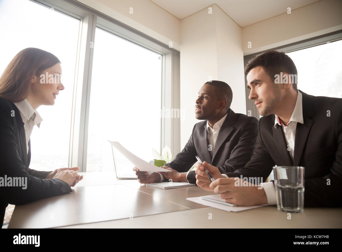 Multinational hiring managers conducting interview with caucasian young woman in formal wear. Millennial female - Stock Image