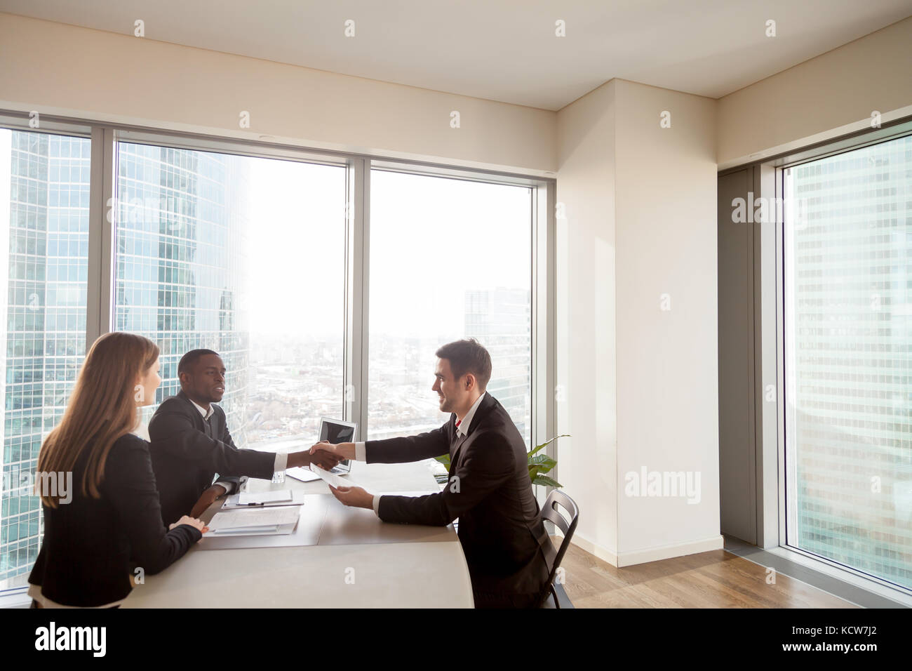 Satisfied multinational business partners celebrating successful negotiations, deal conclusion, profitable agreement. - Stock Image