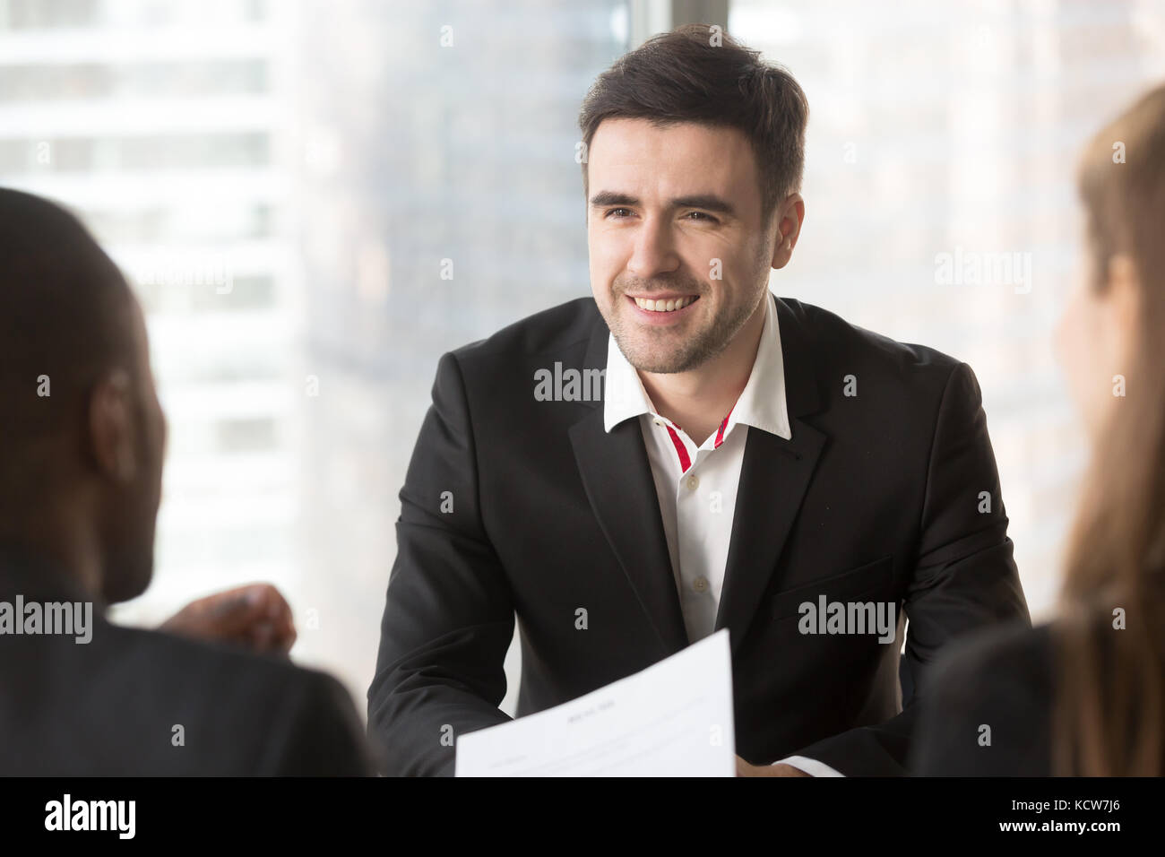 Portrait of confident job candidate talking with multinational interviewers in office, professional specialist communicating - Stock Image