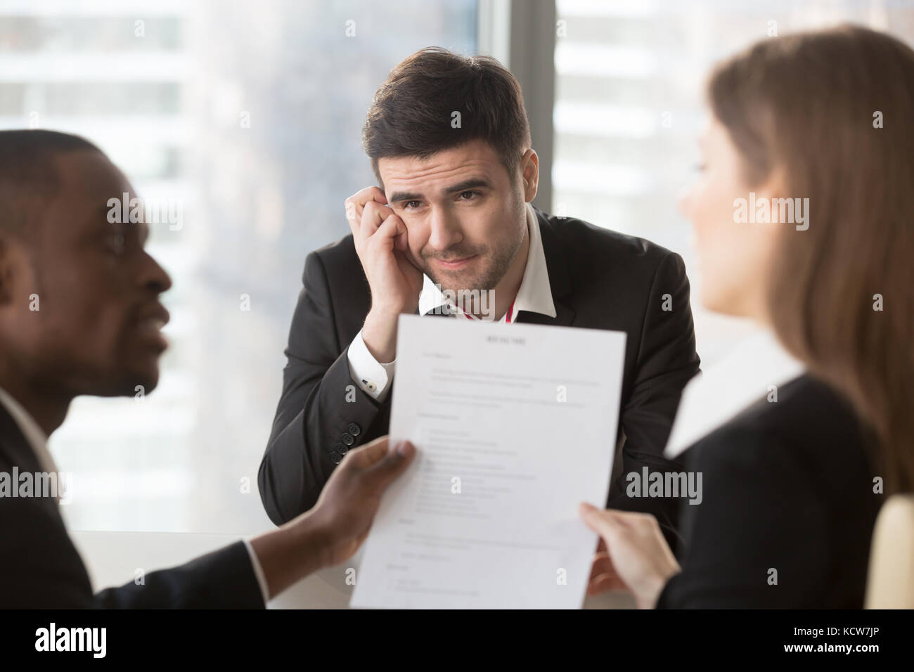 Worried male job candidate interested in company vacancy anxiously looking on multinational recruiters analyzing - Stock Image