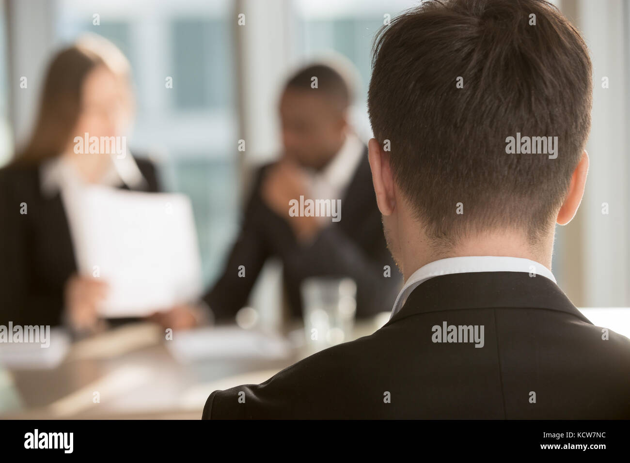 White male job candidate waiting for employers decision, multinational HR managers analyzing resume on background. - Stock Image