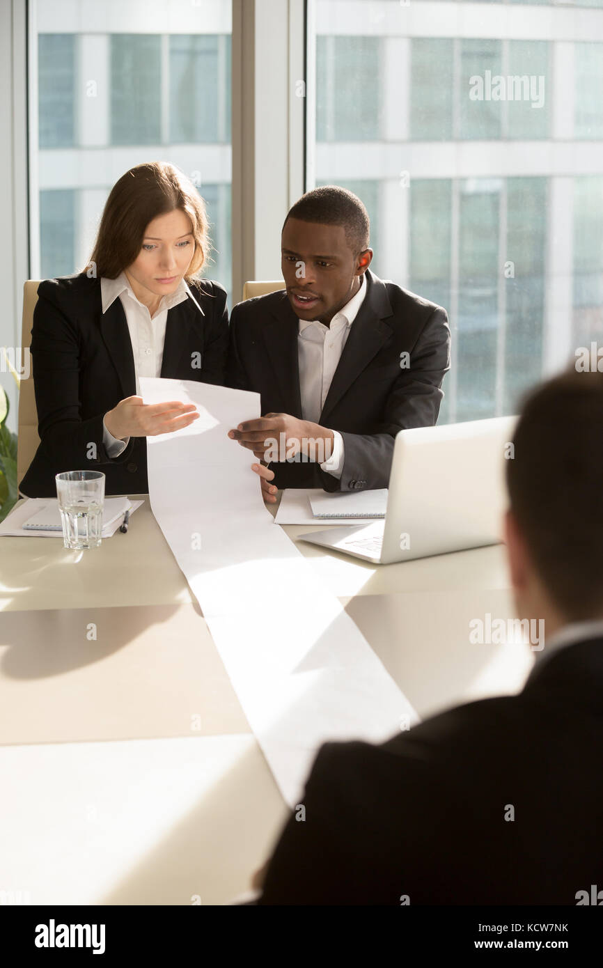African american male and caucasian female employers reading with confusion huge resume, multinational lawyers studying - Stock Image