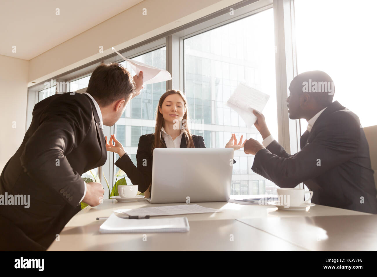 Beautiful funny businesswoman keeping calm in stressful situation at work, refusing pay attention to difficulties - Stock Image