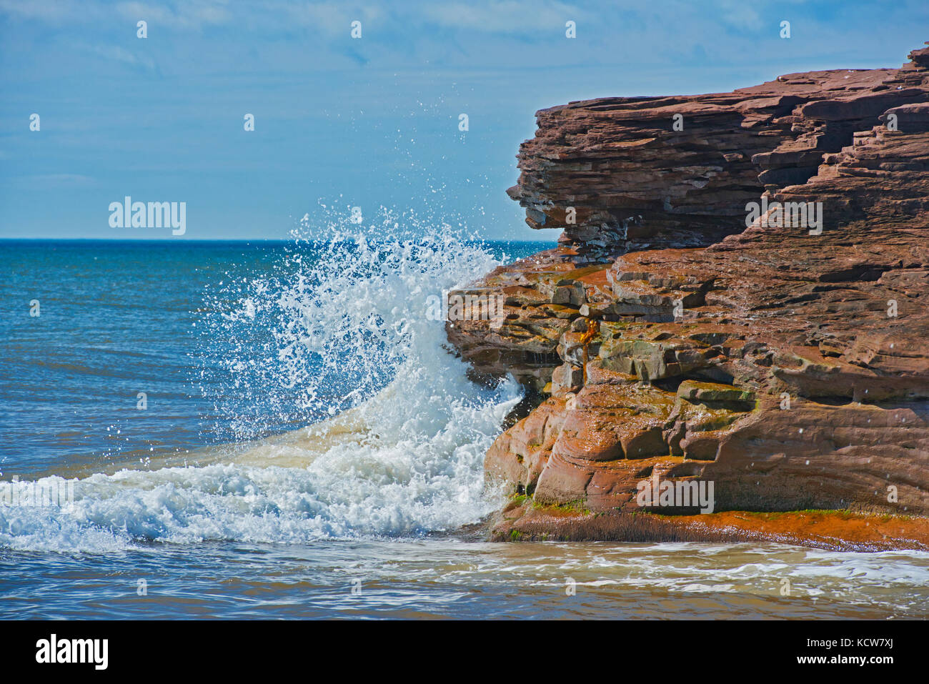 Waves lapping against a rocky outcrop on Lamèque Island, New Brunswick, Canada - Stock Image