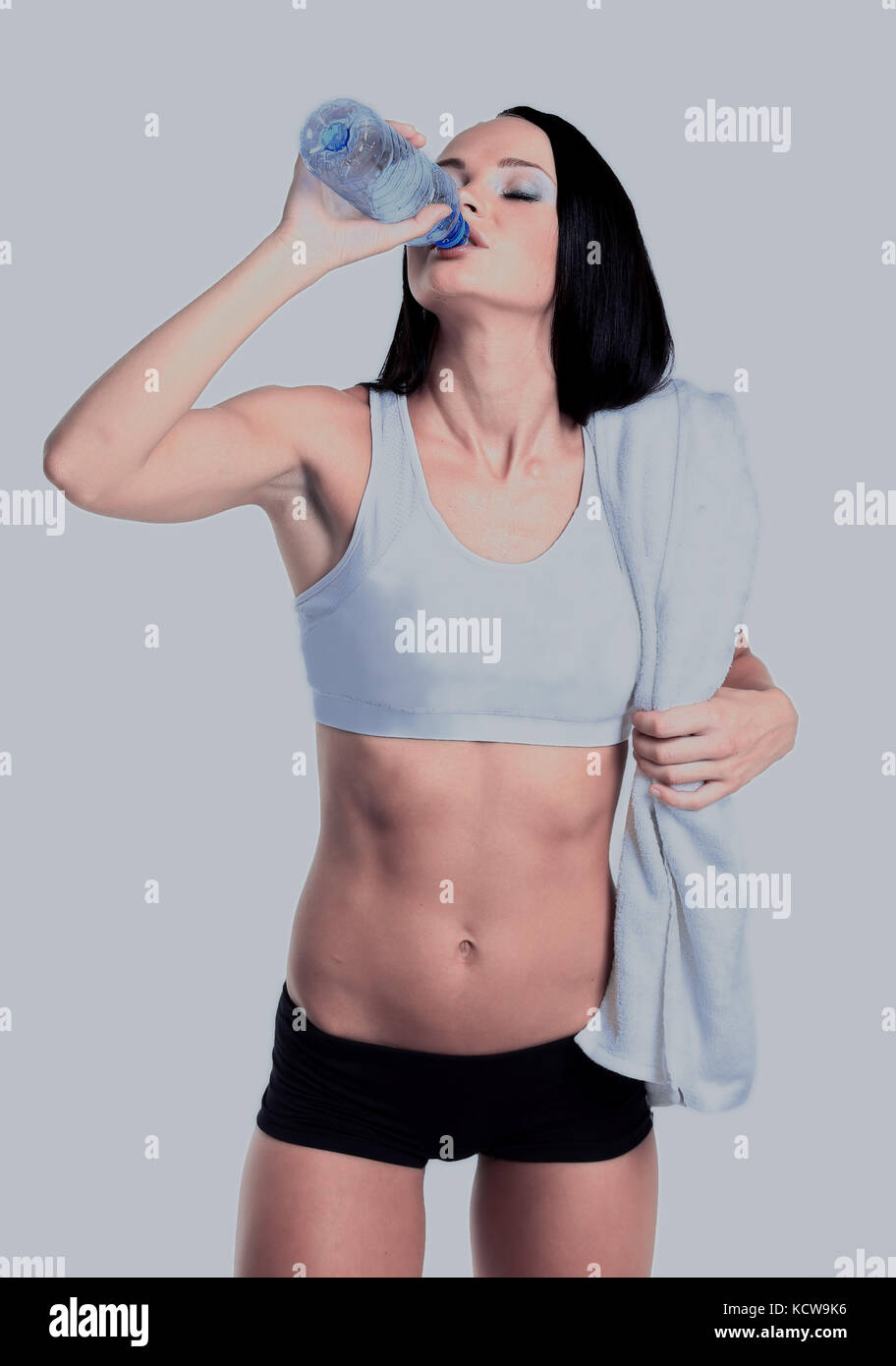 happy smiling woman in sportswear drinking water, isolated over white background - Stock Image