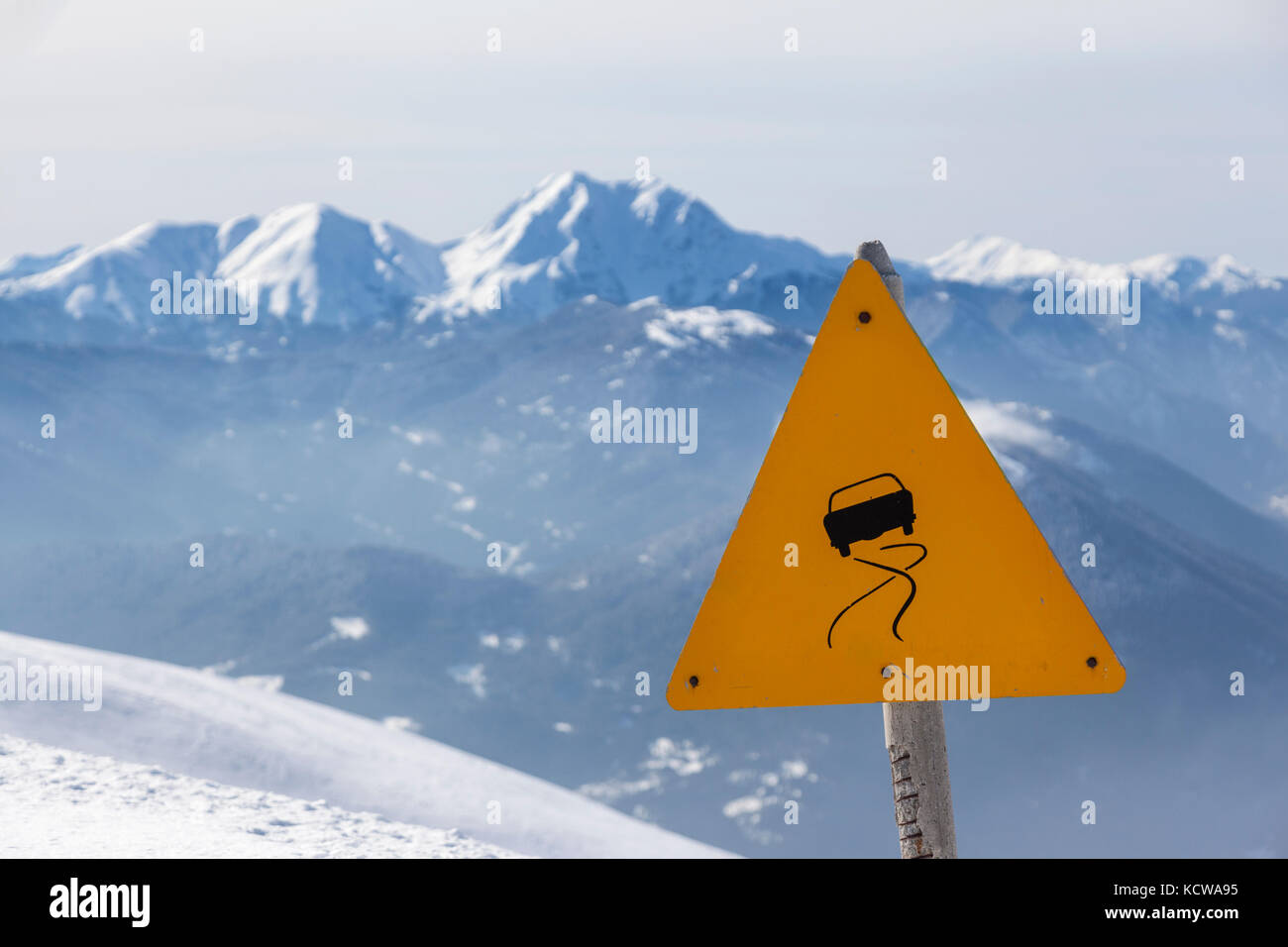 Slippery road sign, in winter landscape and mountains of snow. - Stock Image