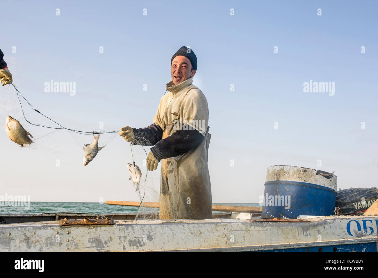 Fishermen from Tastubek embark usually in small boats. Omirserik Ibragimov is 23 years old, he works with his friend - Stock Image