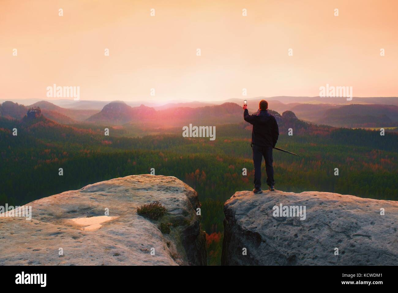 Hiker stand with smart phone on top of mountain and enjoying spring sunrise. Tourist guide with trekking poles. - Stock Image