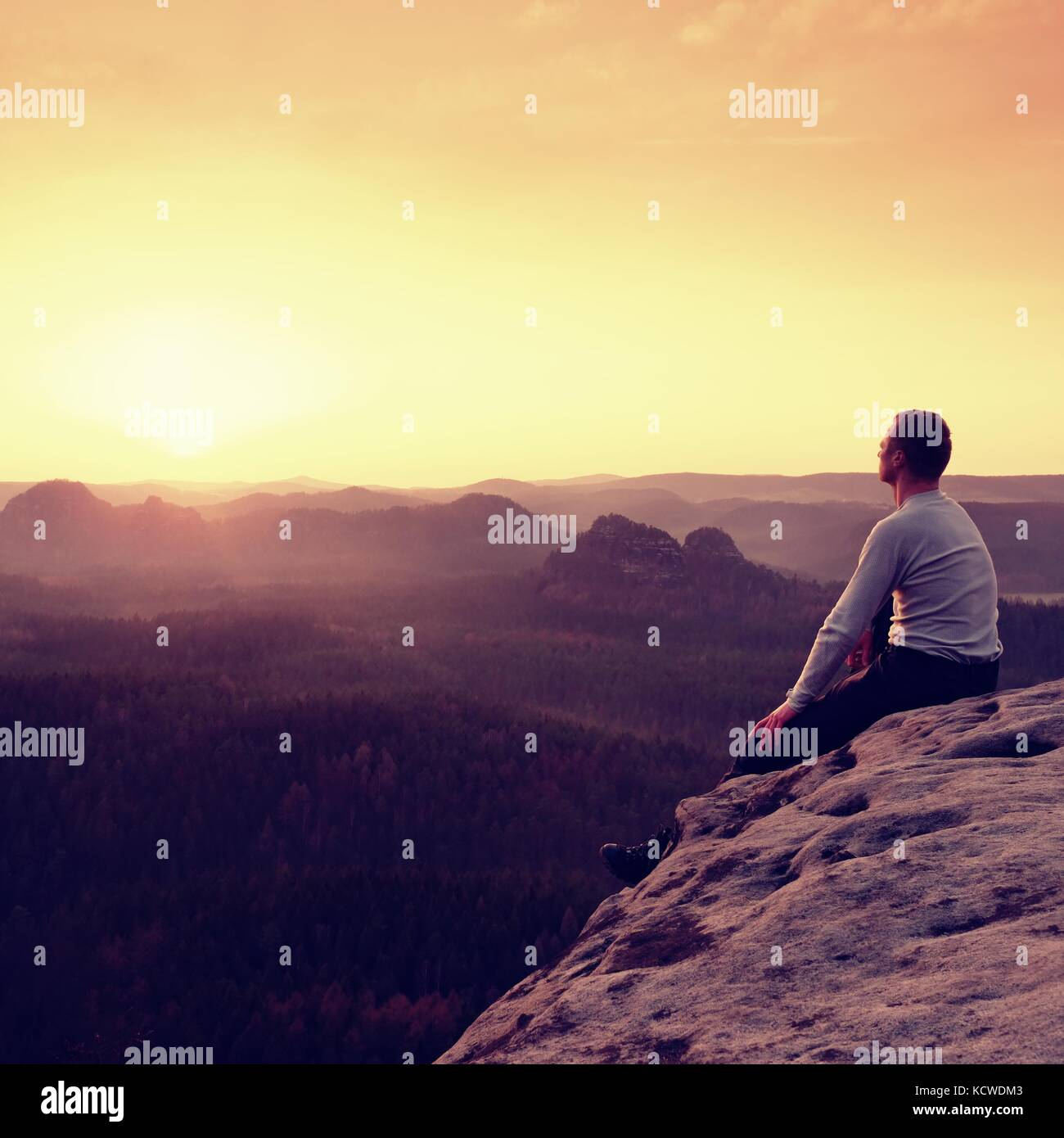 Man sit on the peak of rock and watching into colorful mist and fog in forest valley. Hiker enjoying view of morning - Stock Image