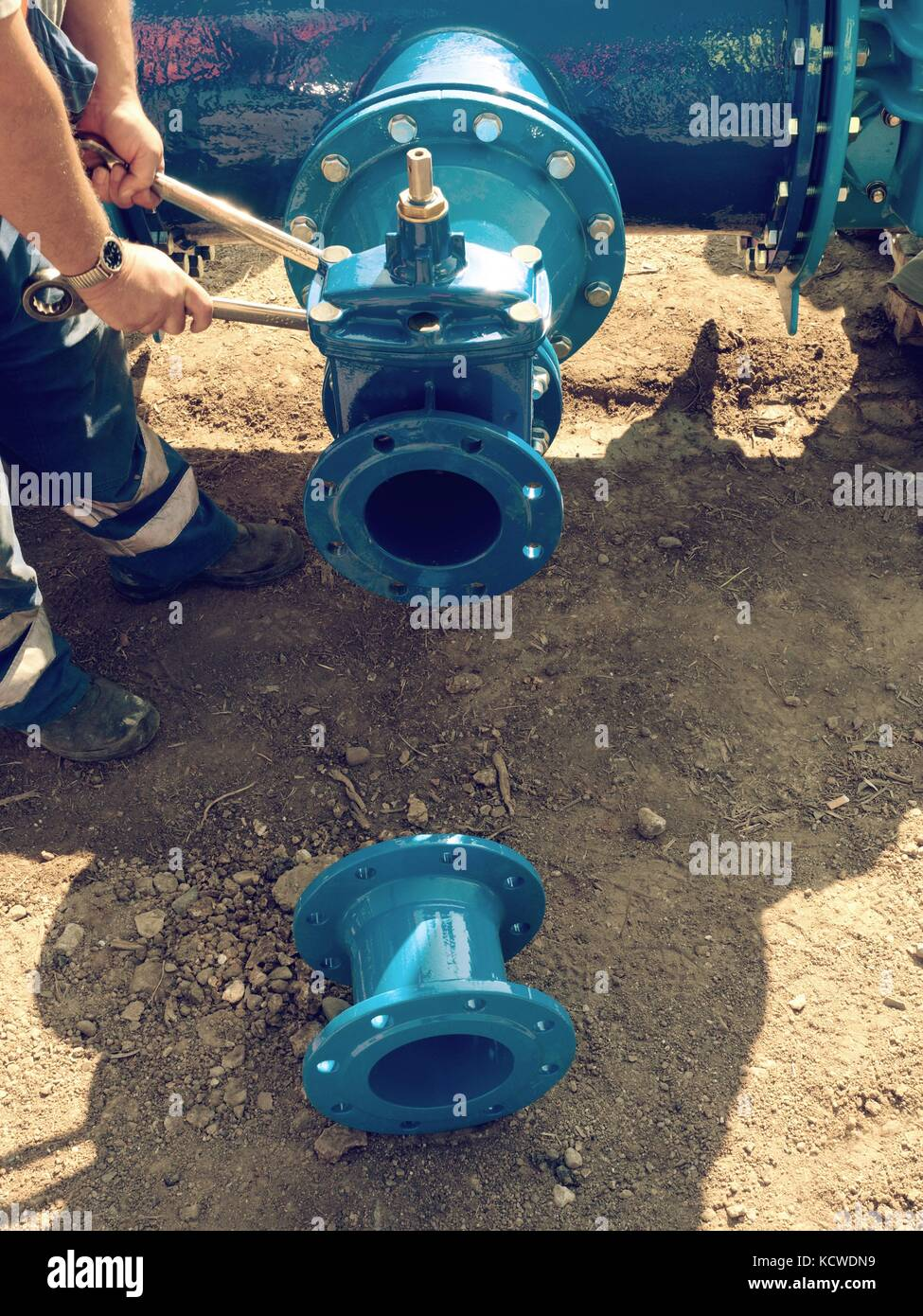 Worker hands with tools screwing  nuts on new dring water piping.   Piping with new Gate valves and reduction member. - Stock Image