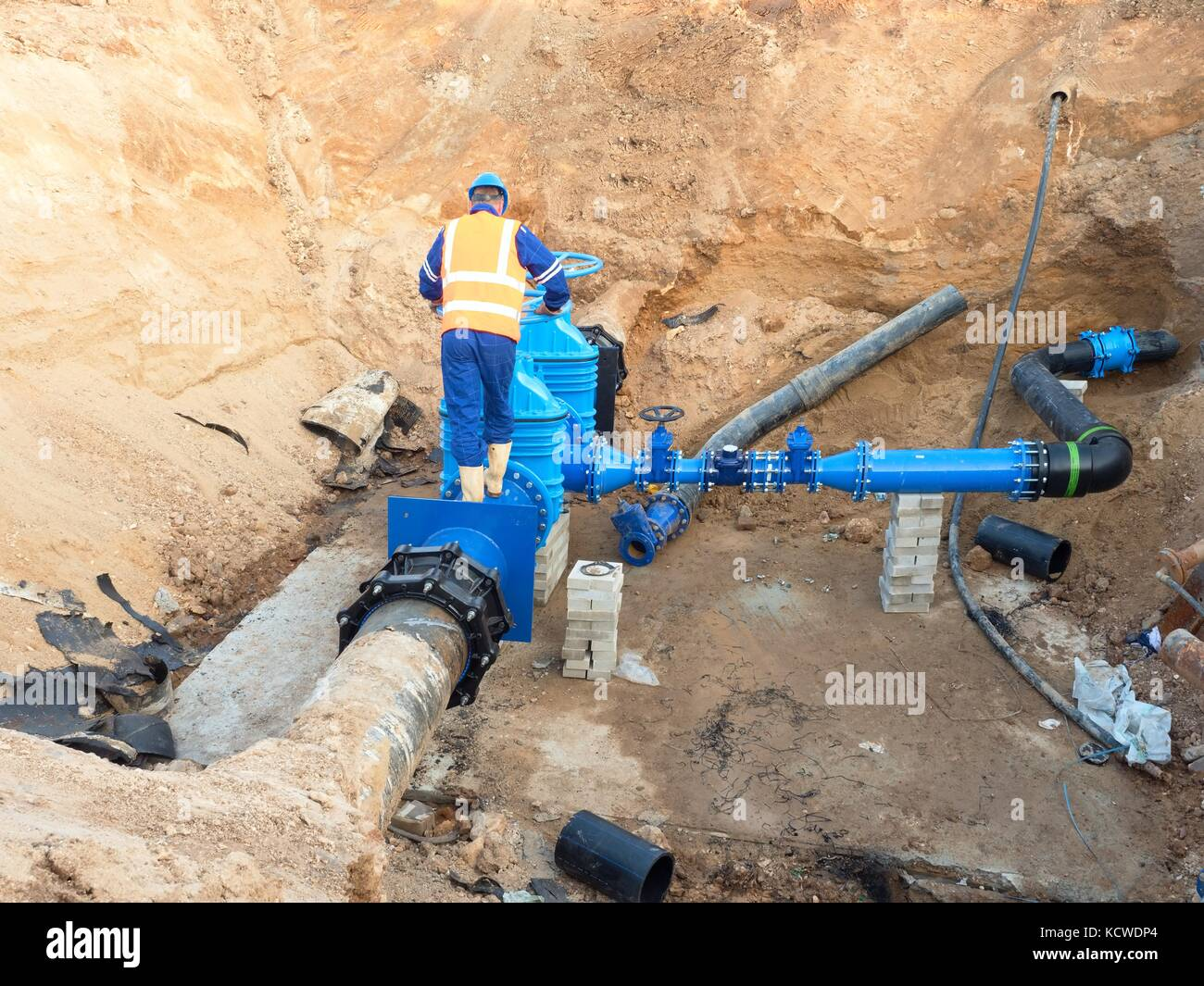 Main City water supply pipeline. Technical staff in reflective vest underground drive pipe gate.  Repaired pipeline - Stock Image