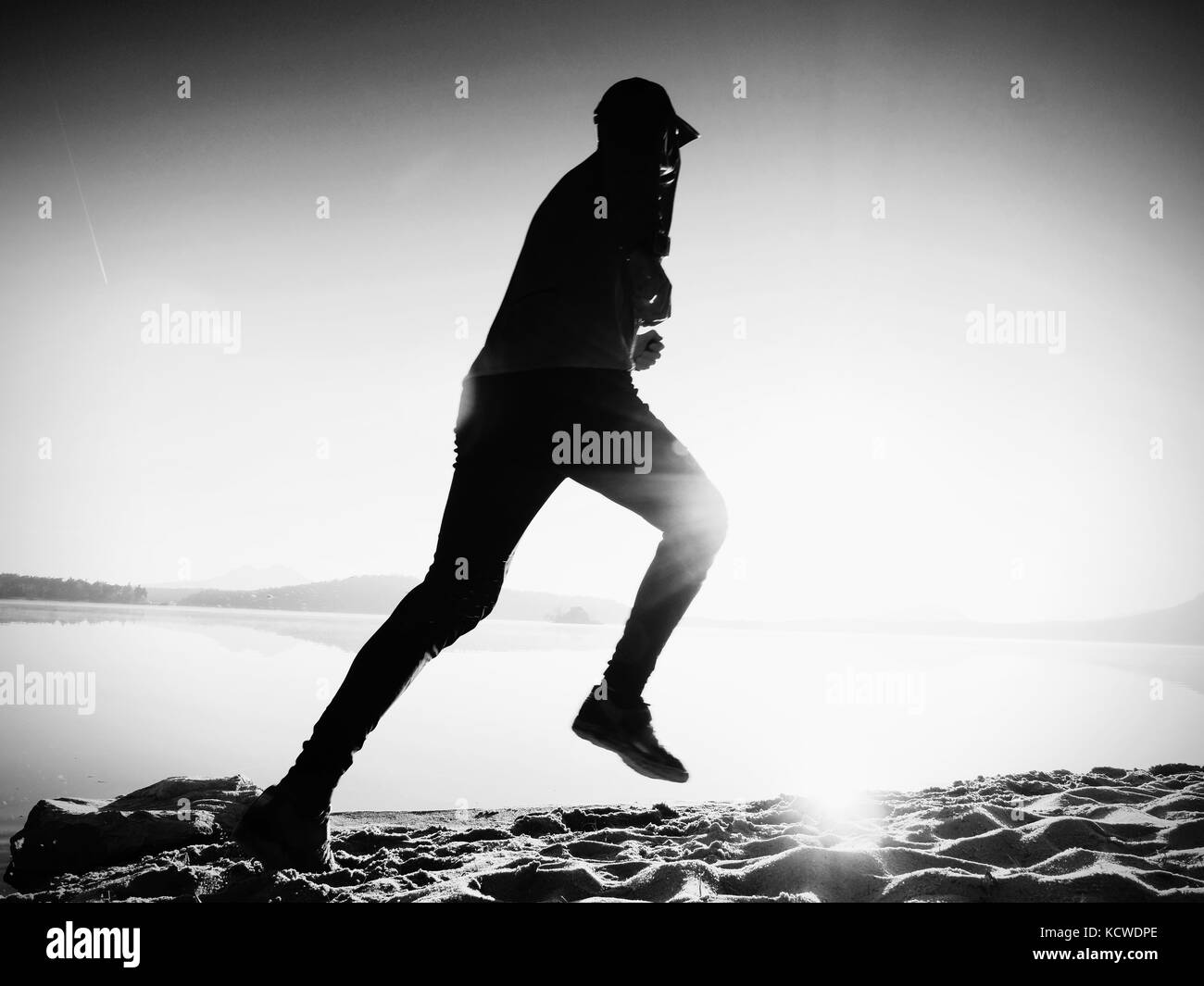 Slim young fitness man runner on beach, tropical trail runner.  Cheerful sportsman run on beach among the water, - Stock Image