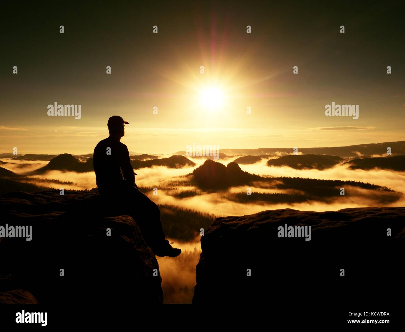 Moment of loneliness. Man with cap sit on the peak of rock and watching into colorful mist and fog in forest valley. - Stock Image