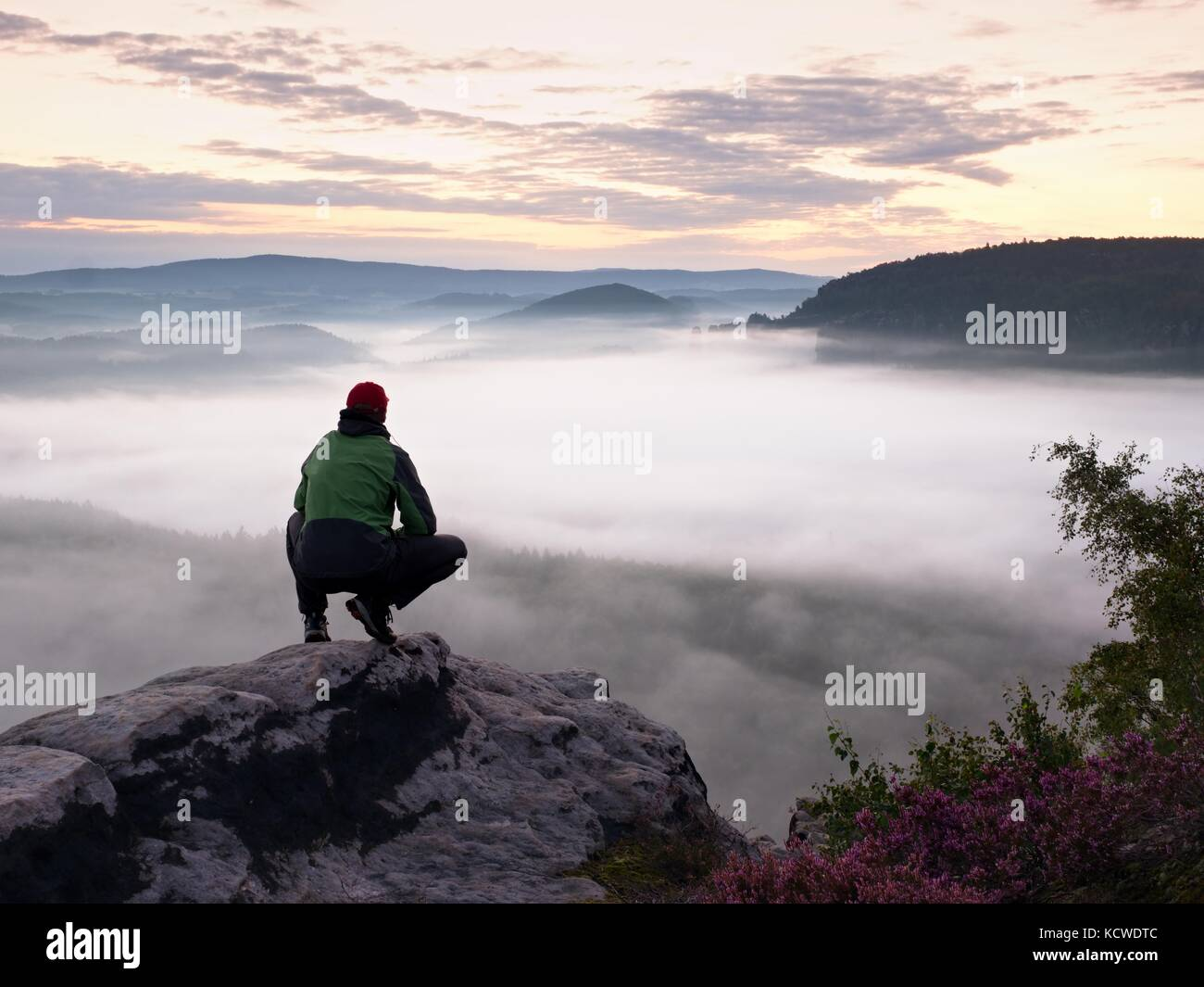 Tourist in red cap and in green black sportswear in squatting position on a rock, enjoy autumn scenery - Stock Image