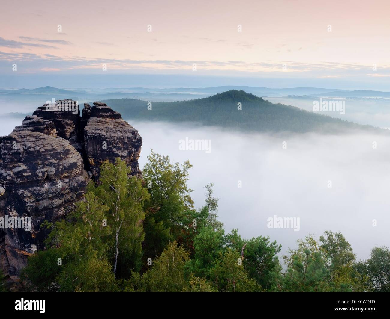 Sharp sandstone cliffs above deep misty valley. Popular climbers resort. Rocks sticking up from fogy lanscape to - Stock Image