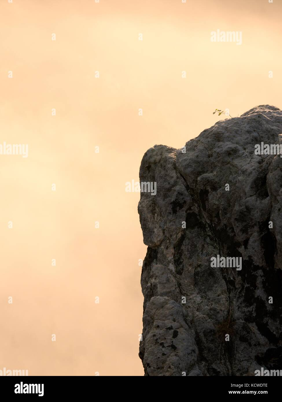 Sharp sandstone cliffs above deep misty valley. Rocks sticking up from fogy lanscape to sky.  Soft focus. - Stock Image