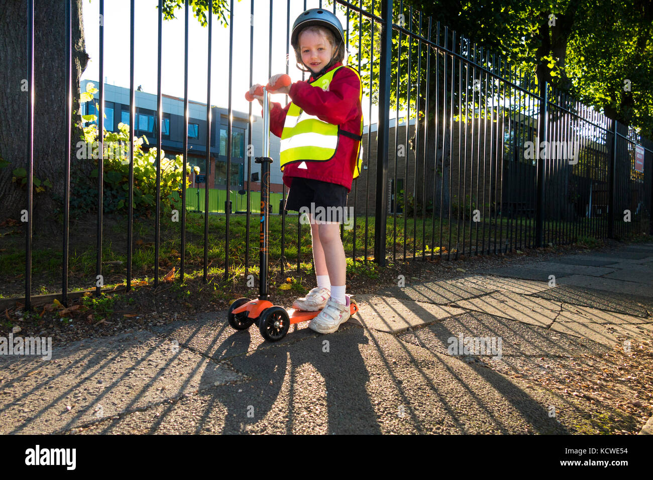 Year 1 pupil / child / girl on scooter in hi vis / high visibility vest jacket scootering / going / scootering to - Stock Image