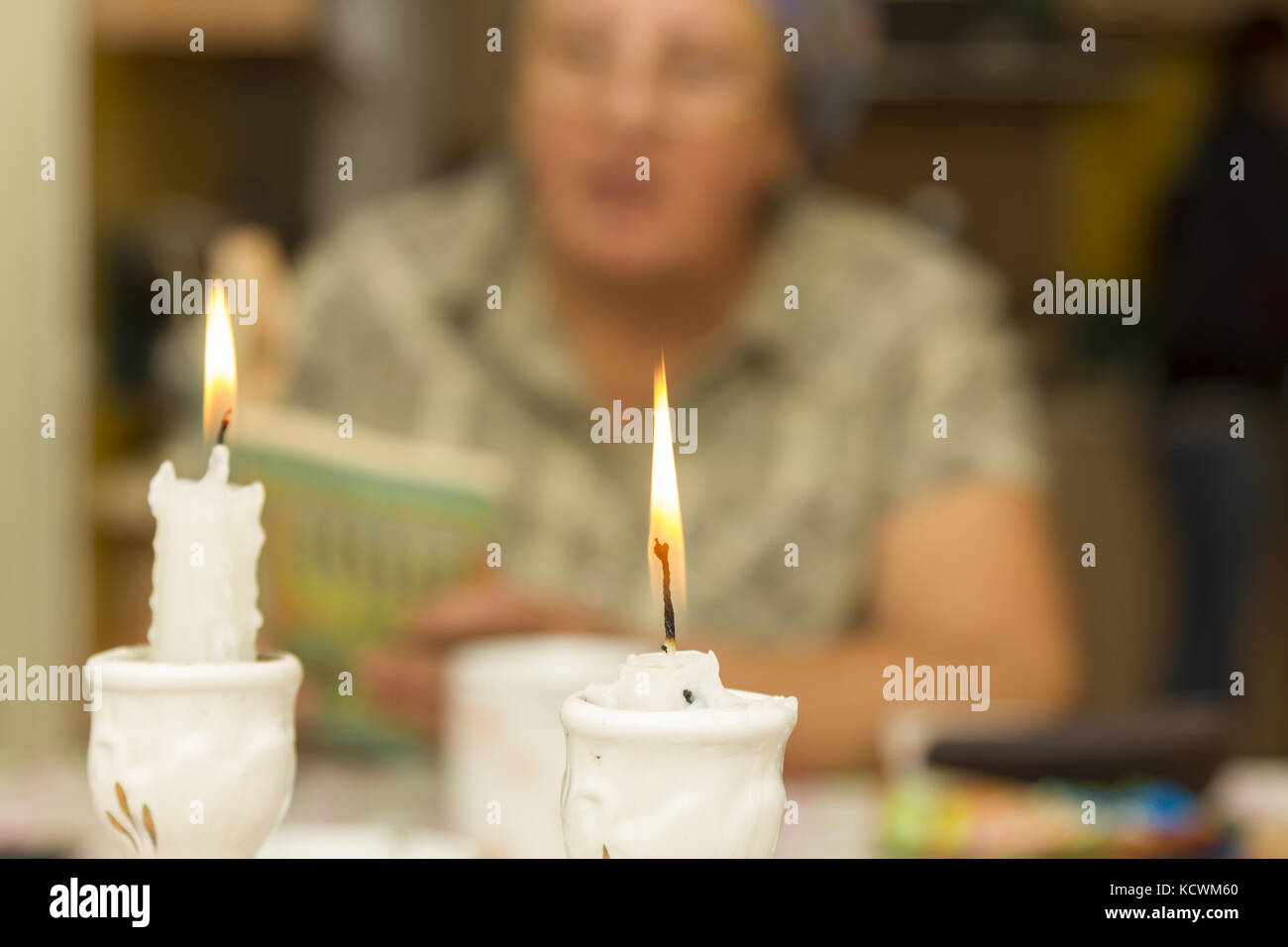 Two Shabbat Candles Against the background of a woman reading the Torah - Stock Image
