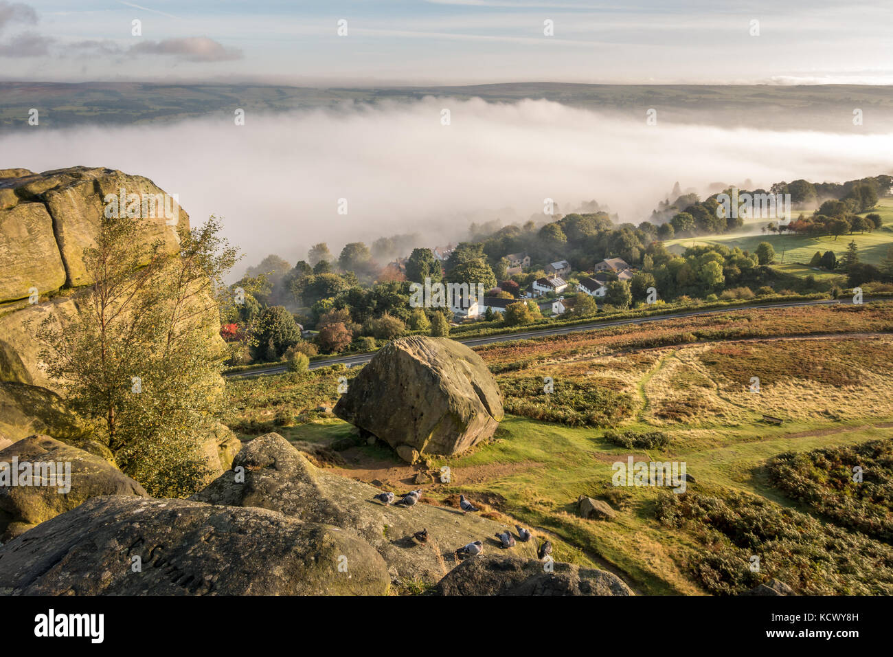 An unusual dramatic viewpoint of the Cow and Calf Rocks on rural Ilkley Moor with a cloud inversion in the Wharfedale - Stock Image