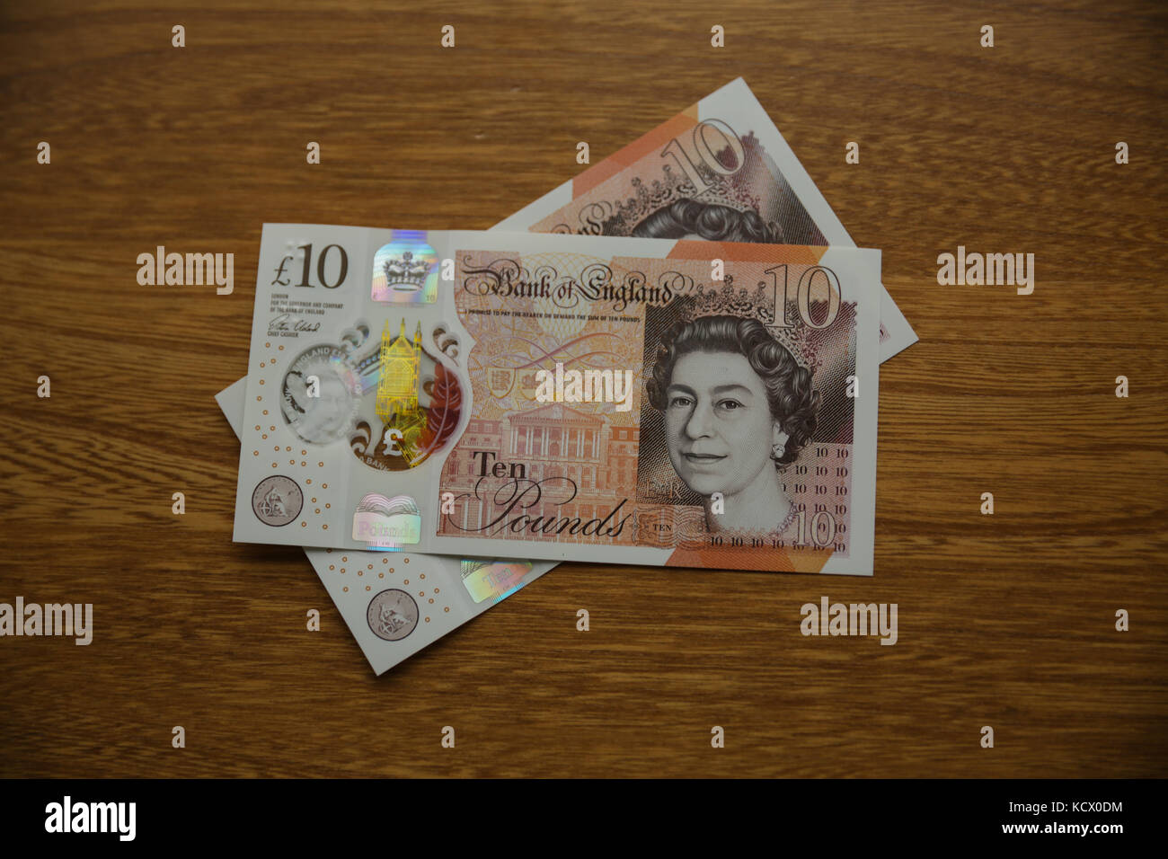 The NEW British Ten Pound note on a wooden surface from above - Stock Image