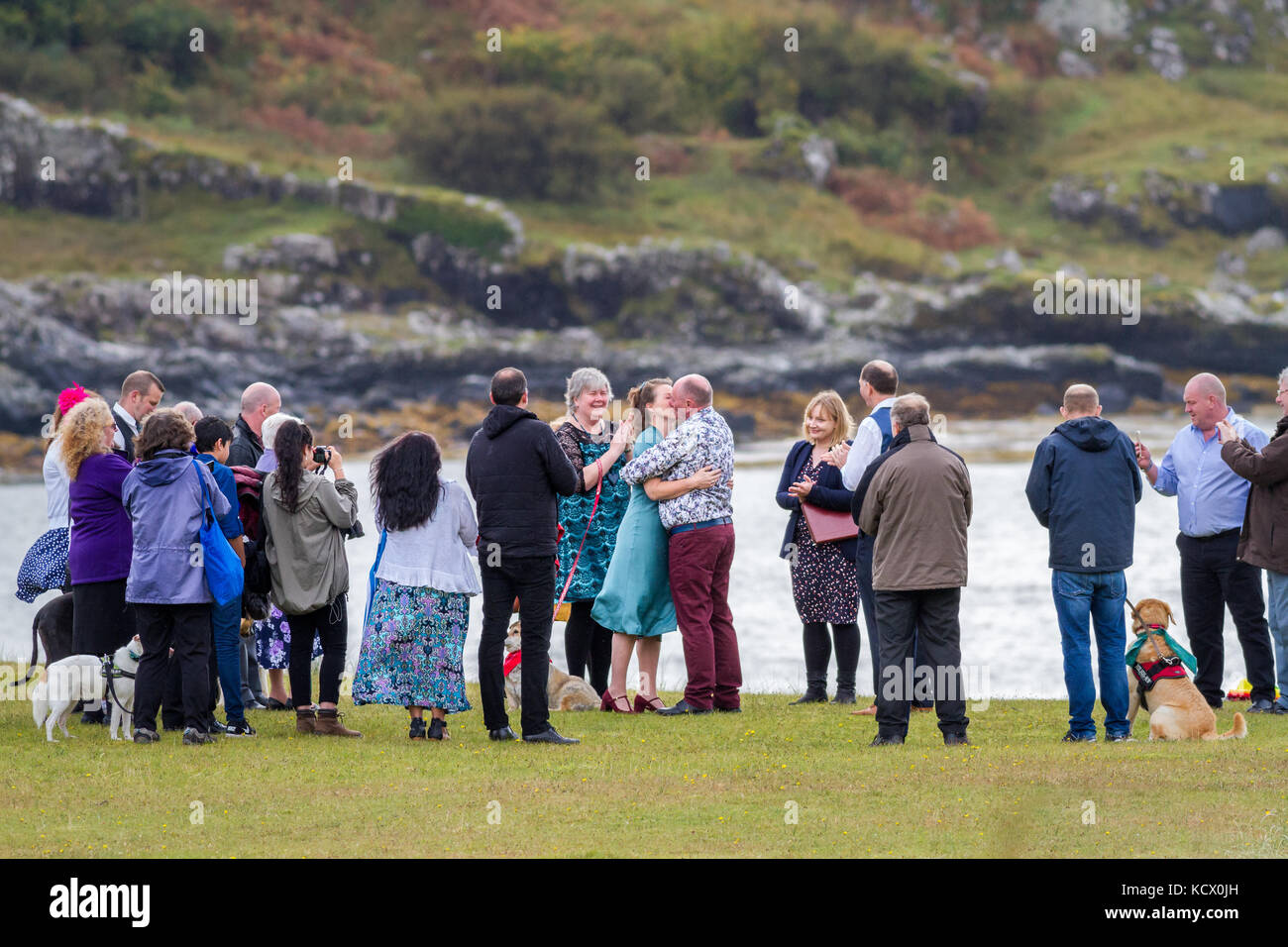 Wedding ceremony taking place outside with bride and groom kissing, Calgary Bay, Isle of Mull, Scotland, UK - Stock Image