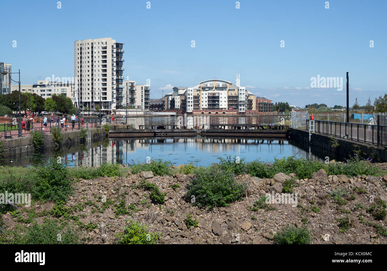 Earth dam across entrance to Roath Basin in former Cardiff Docks with new apartments redeveloped on former dockland - Stock Image