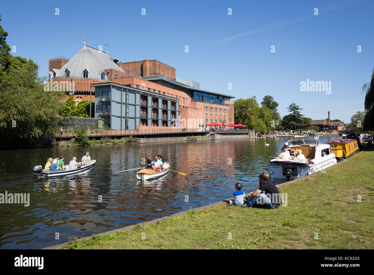 Rowing boats on the River Avon with the Royal Shakespeare Theatre, Stratford-upon-Avon, Warwickshire, England, United - Stock Image