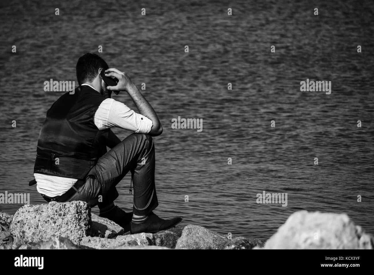 Man phoning at seaside - Stock Image
