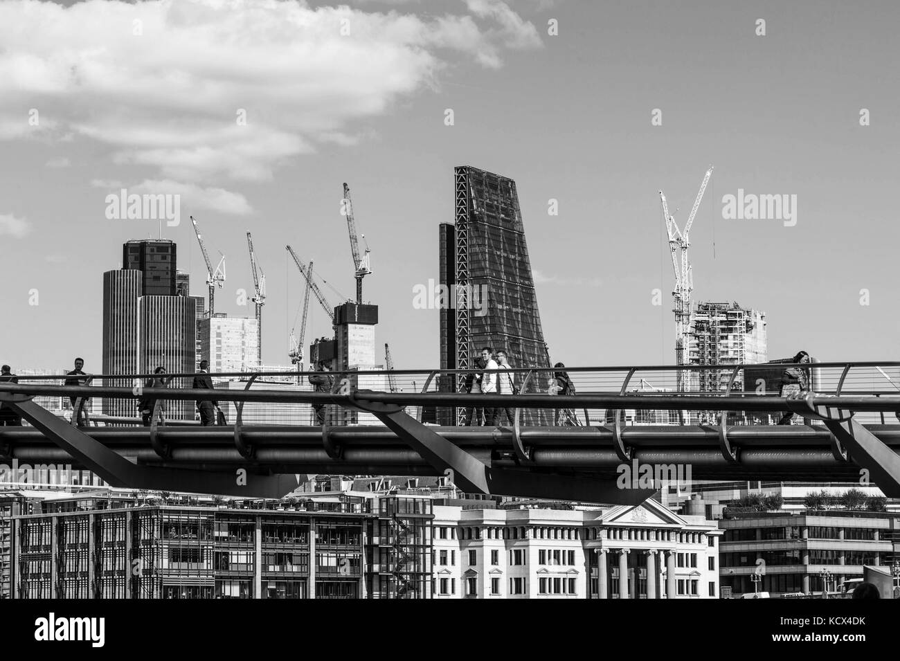Black and White Monochrome Image of People Walking Across the Millennium Footbridge Across the River Thames In London - Stock Image