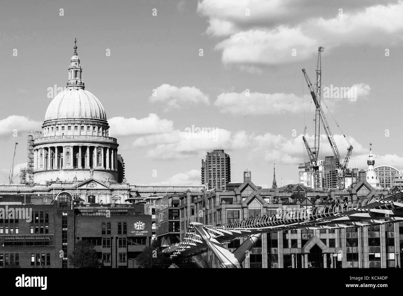 Black and White Monochrome Image of St Pauls Cathedral and the Millennium Footbridge Crossing the River Thames With - Stock Image