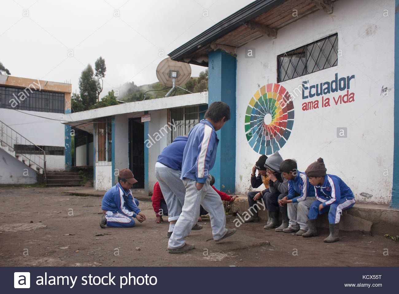 Ecuadorian students playing marbles in the dirt backyard of a school. Education during the Citizen's Revolution. - Stock Image