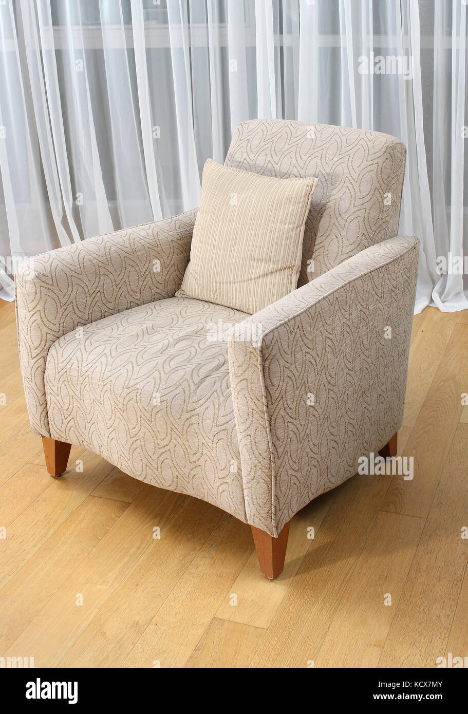 Comfortable armchair with decorative pillow in modern interior - Stock Image