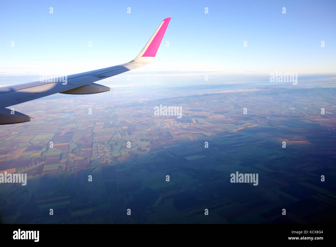 View of window at flying airplane and sky with clouds from top view. Stock Photo