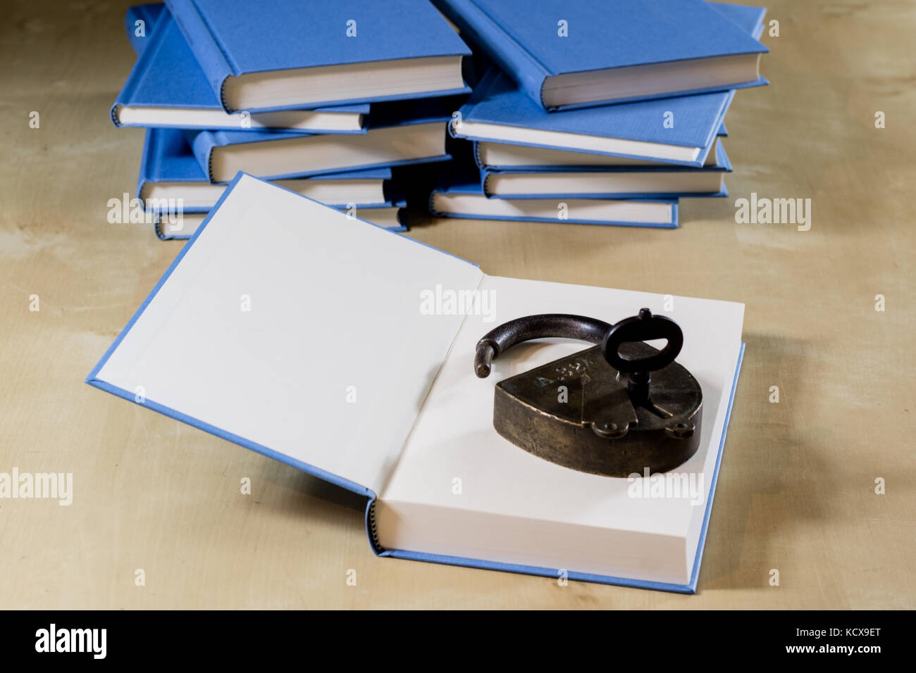 Heap Of Books Reading On A Wooden Table. Beside Lies Padlock. Black  Background.