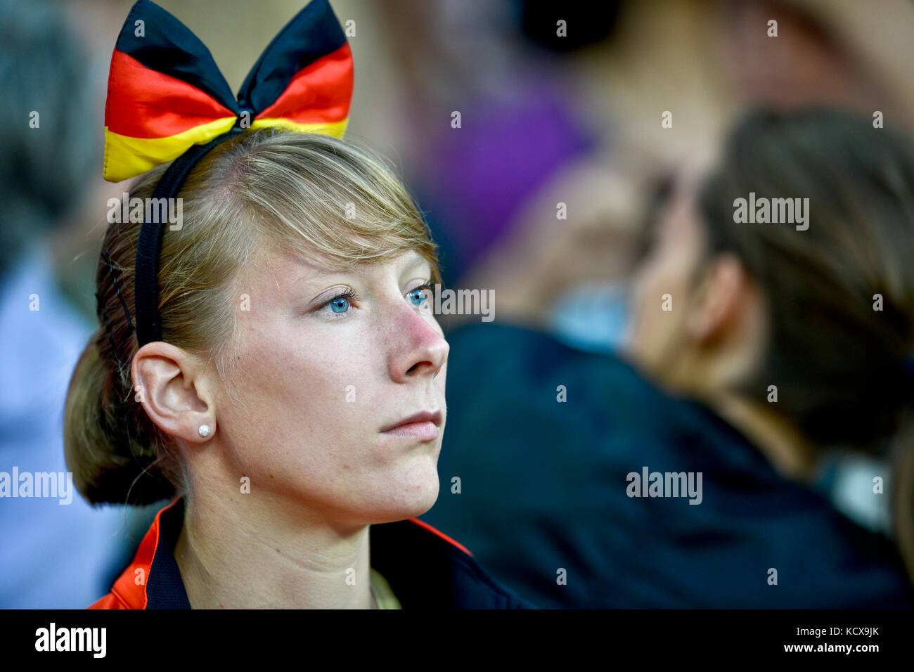 German woman wearing a bow with the German flag - Stock Image