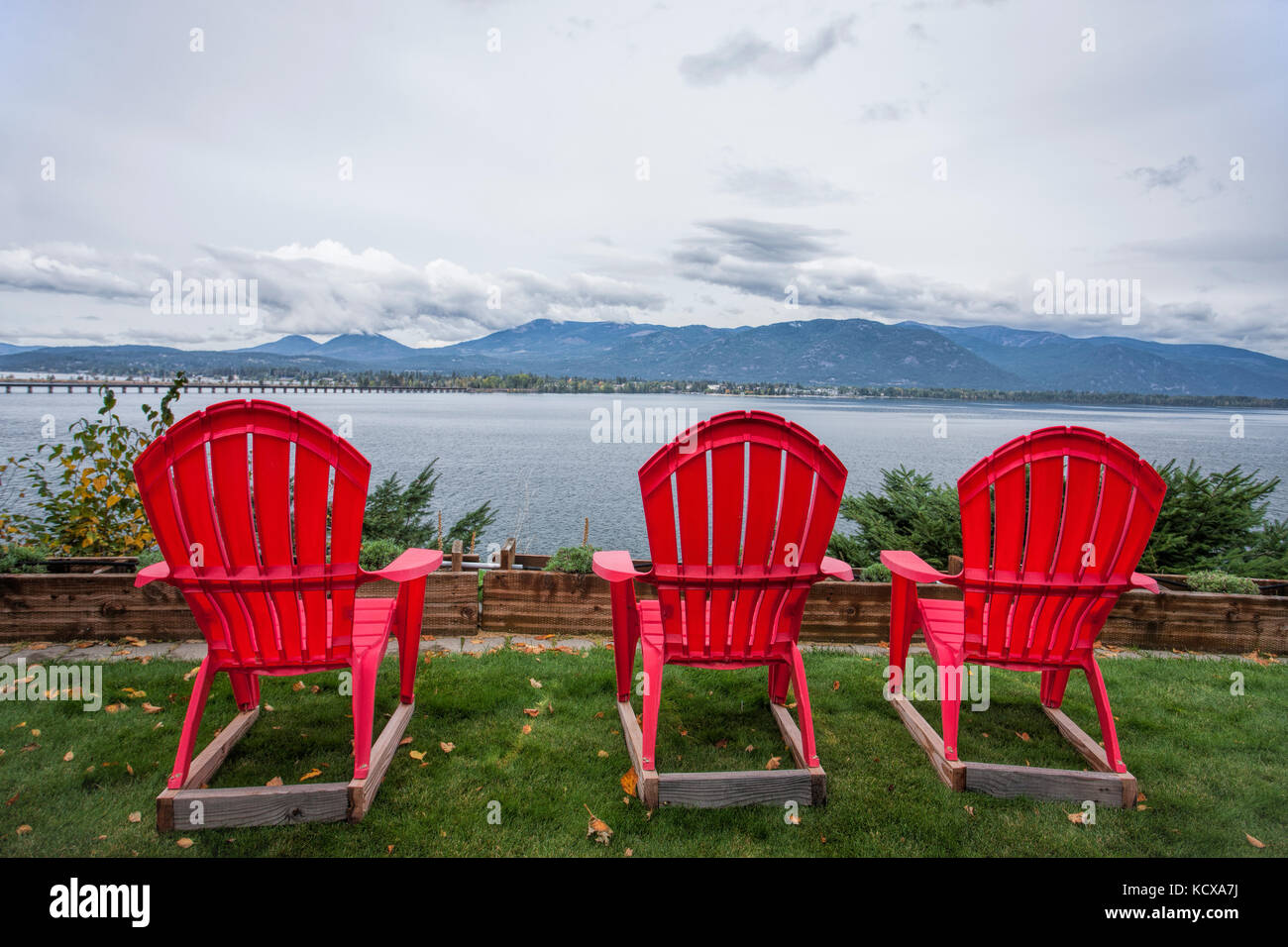Three red lawn chairs sit in the yard overlooking the lake by Sandpoint, Idaho. - Stock Image