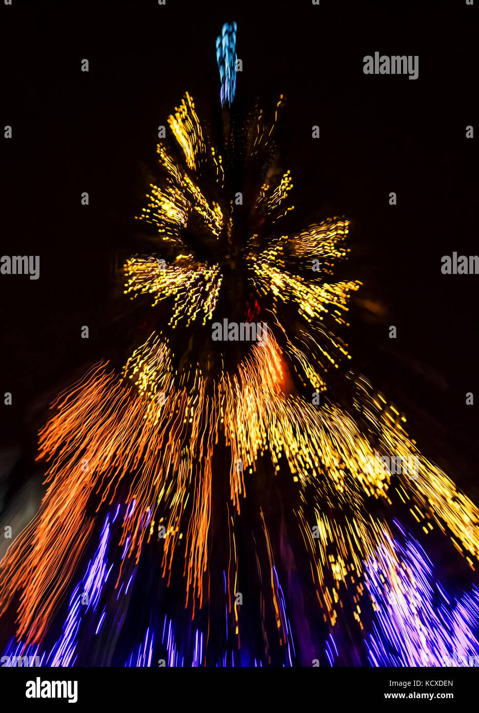 Abstract Christmas lights background at night. Christmas tree blurred with zoom effect - Stock Image