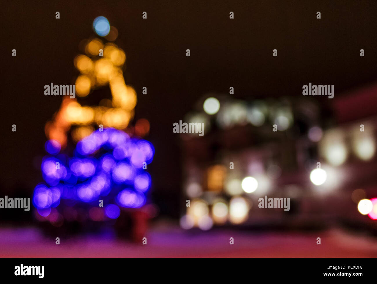 Abstract Christmas lights background at night. Christmas tree on the city square blurred with bokeh effect - Stock Image