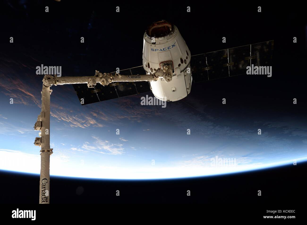 The commercial supply ship SpaceX dragon is grabbed by the CanadaArm2 robotic arm for docking to the International - Stock Image
