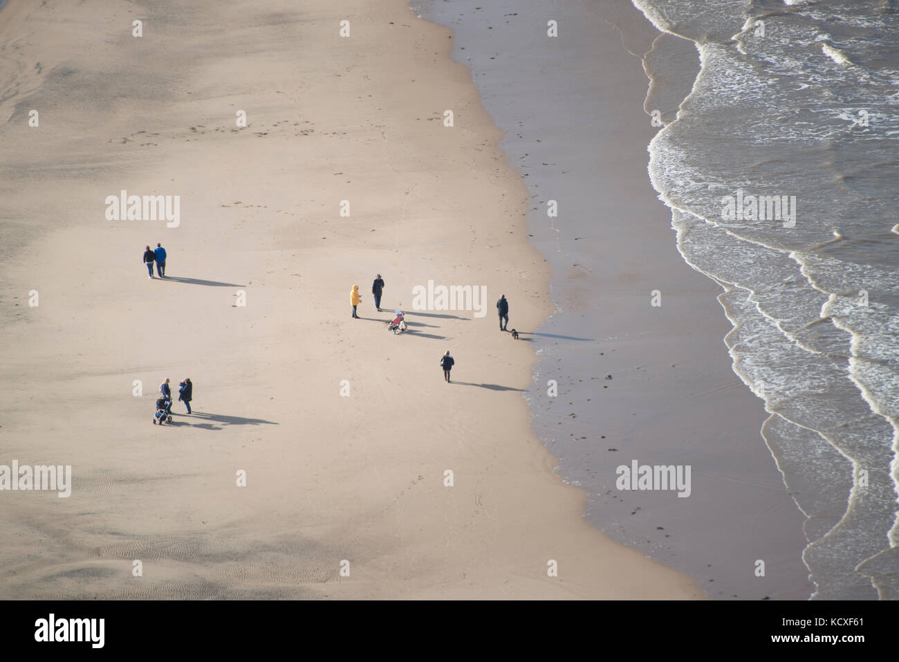 Groups of holiday makers walking along Blackpool beach. Credit: LEE RAMSDEN / ALAMY - Stock Image