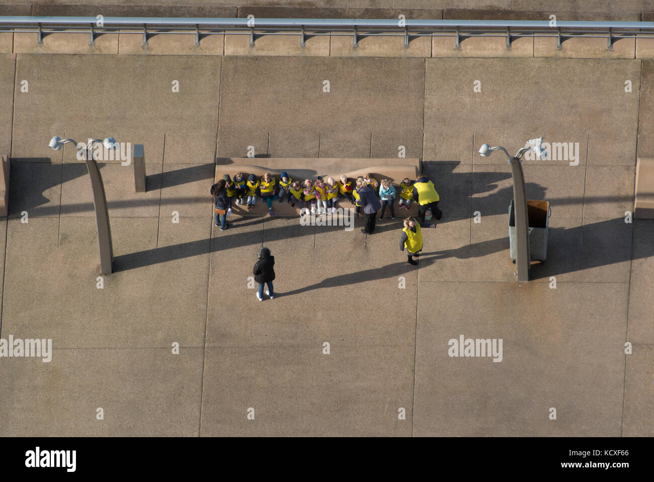 A class of school children on a day out to Blackpool sea front. All sat nicely on a bench wearing yellow bibs. Credit - Stock Image