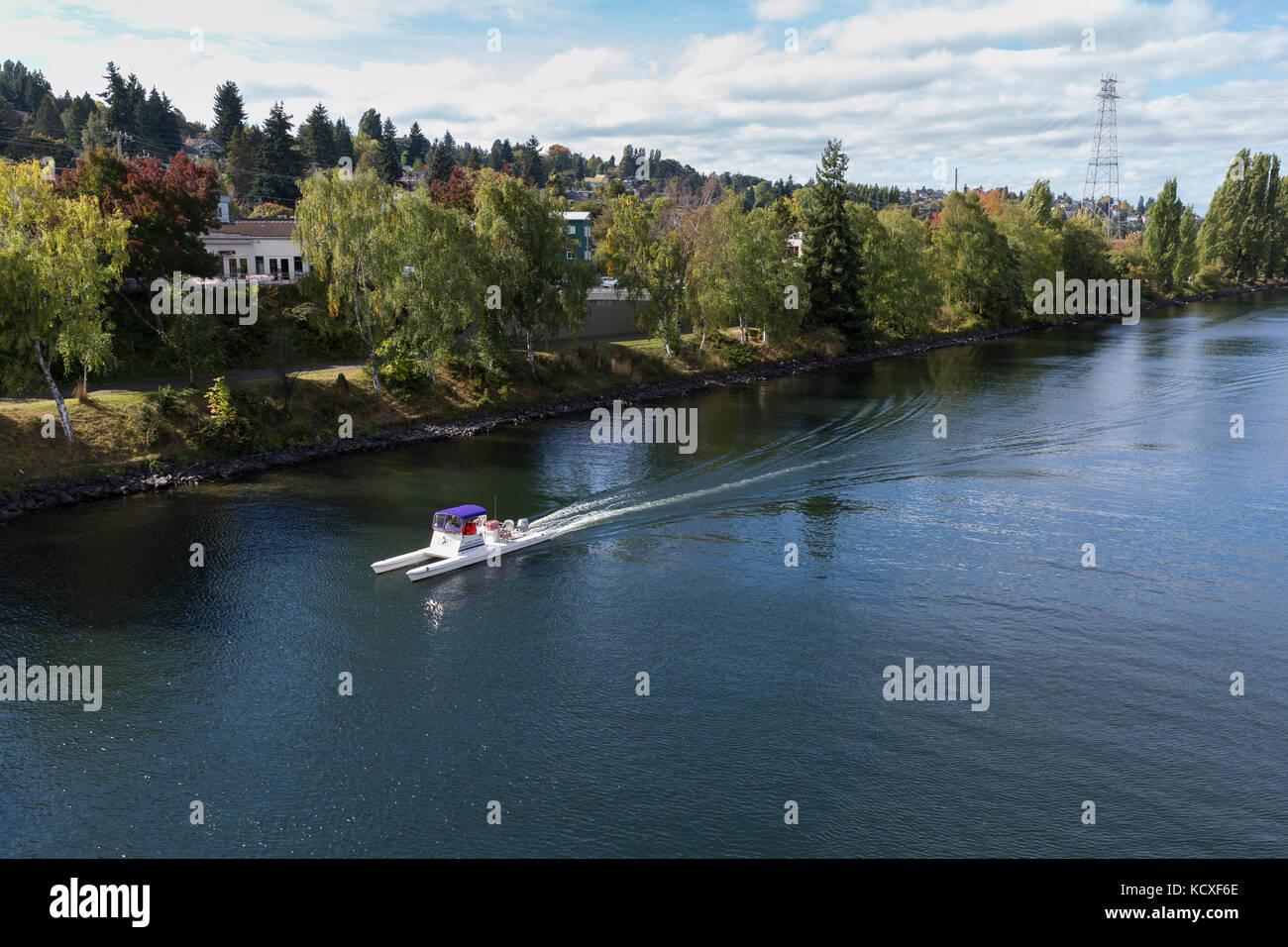 Seattle, Washington: University of Washington coach boat sailing along Fremont Cut towards Lake Union. - Stock Image