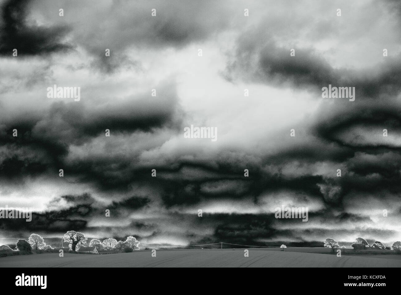 Dramatic sky over fields, with farmhouse, trees and telephone wire visible in foreground, Devon, UK - solarised - Stock Image