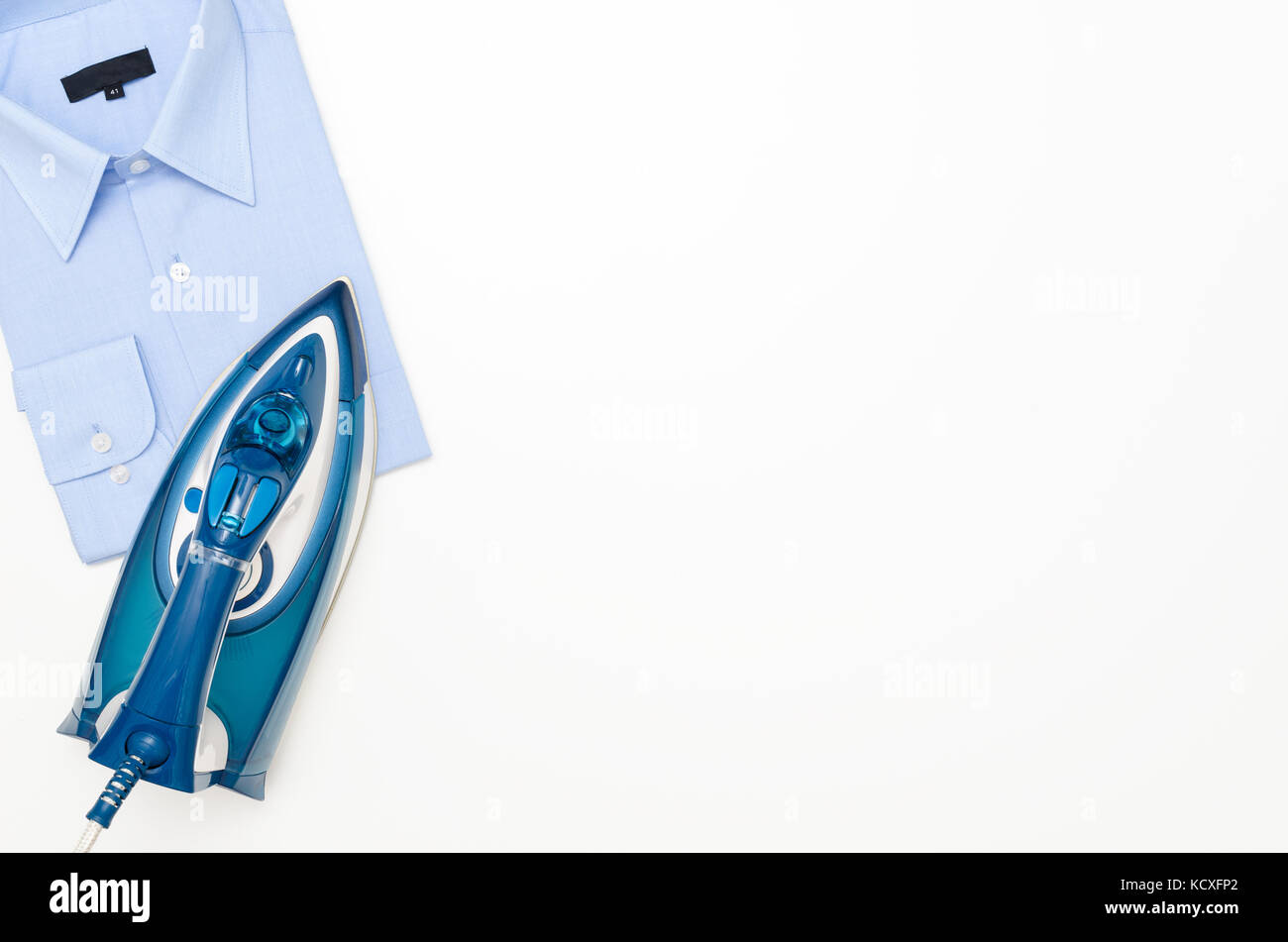 Blue iron and shirt on ironing board top view. iron board clothes ironing shirt household appliance electric concept - Stock Image