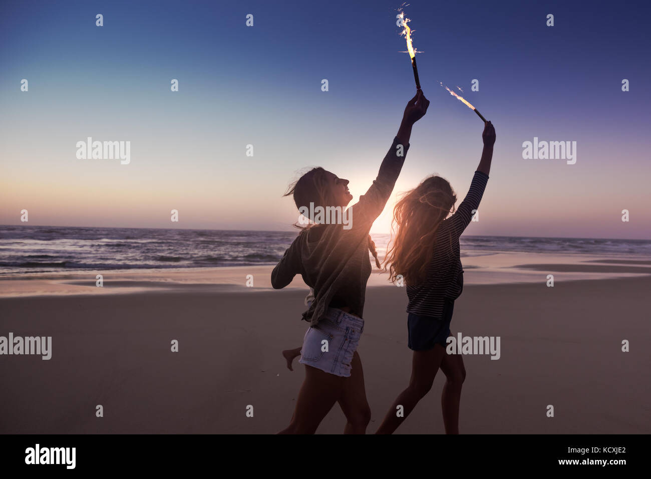 Teenage friends running on a beach with fireworks - Stock Image